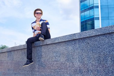 Stylish young man eating take away food in downtown