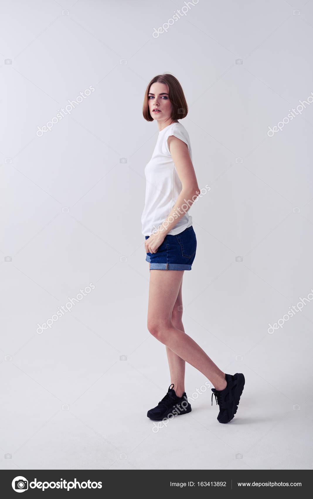 9d2262935d Cuerpo entero mujer joven de linda chica posando en shorts de jeans y  camiseta blanca con espacio de copia - mujer guapa cuerpo completo — Foto  de ...