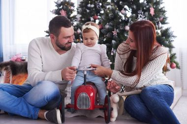 Little daughter sitting on retro toy car with parents near Chris