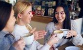 Přátelé se těší konverzaci a pití kávy v kavárně