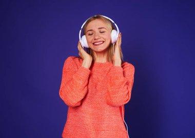 happy blond enjoying music in headphones