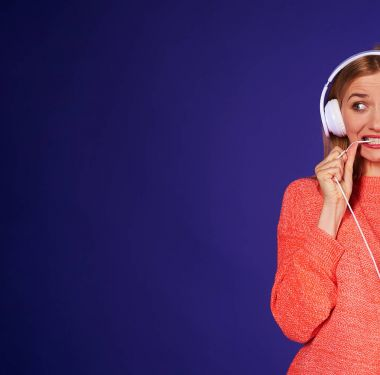 cropped image of funny blond biting cord of headphones