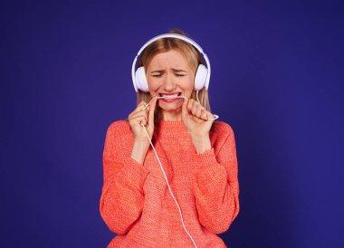 upset woman in headphones biting cord