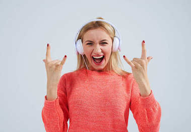 young blond listening rock music in headphones