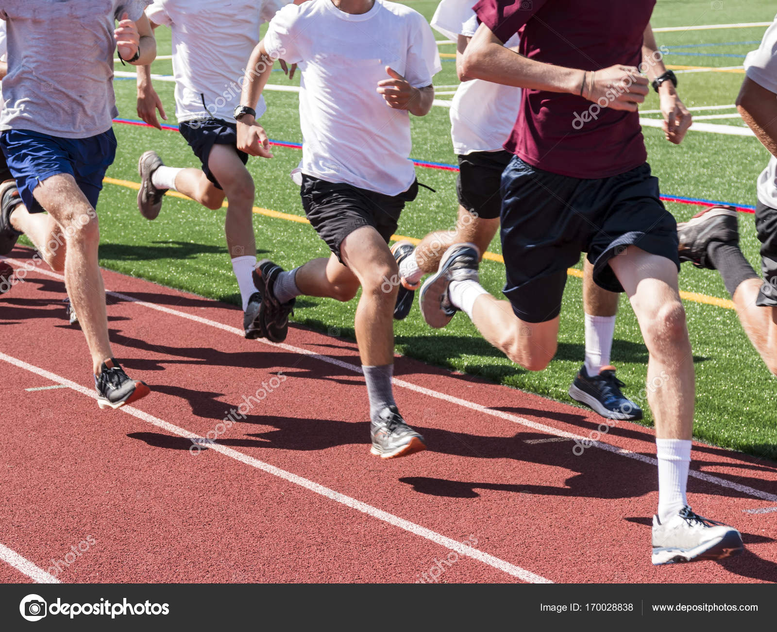 Boys running fast on a track in a group
