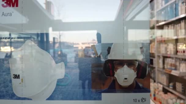 Istanbul, Turkey - March 3, 2020 : A 3M brand medical mask on a pharmacy display window from close up, reflections of the walking people at the street are visible  on the window glass.