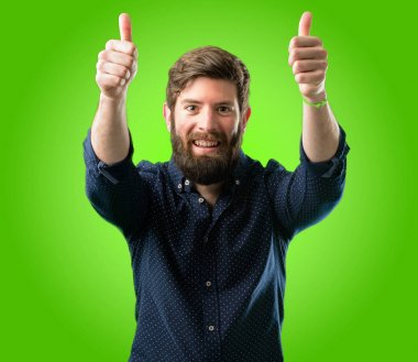 Young hipster man with big beard stand happy and positive with thumbs up approving with a big smile expressing okay gesture over green background