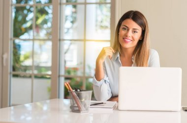 Student woman at table with laptop at home confident and happy with a big natural smile laughing