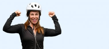 Middle age cyclist woman using earphones happy and excited celebrating victory expressing big success, power, energy and positive emotions. Celebrates new job joyful isolated blue background