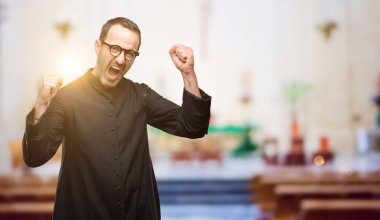 Priest religion man happy and excited celebrating victory expressing big success, power, energy and positive emotions. Celebrates new job joyful at church