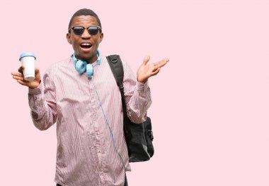 African black man student happy and surprised cheering expressing wow gesture