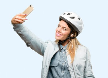 Young woman with bike helmet and earphones happy talking using a smartphone mobile phone