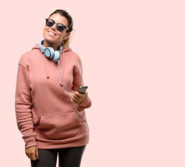 Young sport woman with headphones and sunglasses happy and surprised cheering expressing wow gesture pointing up