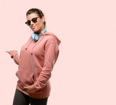 Young sport woman with headphones and sunglasses happy showing love with hands in heart shape expressing healthy and marriage symbol