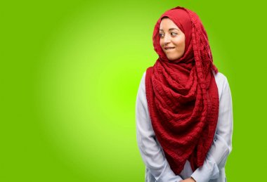 Young arab woman wearing hijab confident and happy with a big natural smile looking side