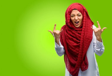 Young arab woman wearing hijab making rock symbol with hands, shouting and celebrating
