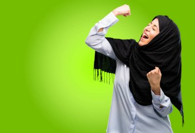 Young arab woman wearing hijab happy and excited celebrating victory expressing big success, power, energy and positive emotions. Celebrates new job joyful
