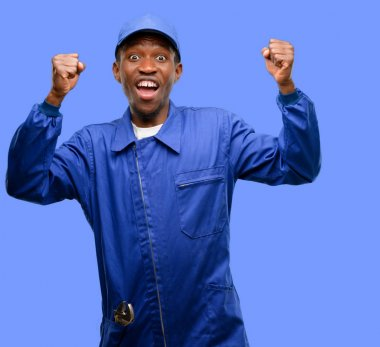 African black plumber man happy and excited celebrating victory expressing big success, power, energy and positive emotions. Celebrates new job joyful