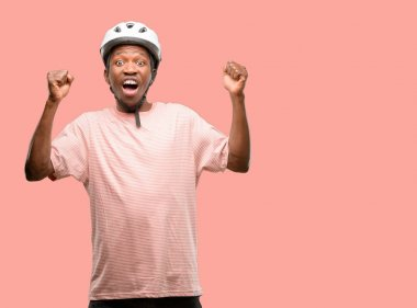 Black man wearing bike helmet happy and excited celebrating victory expressing big success, power, energy and positive emotions. Celebrates new job joyful