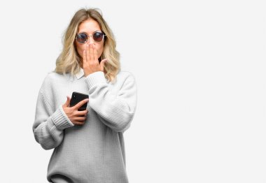 Young beautiful woman using smartphone covers mouth in shock, looks shy, expressing silence and mistake concepts, scared