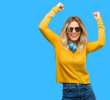 Young beautiful woman with headphones happy and excited celebrating victory expressing big success, power, energy and positive emotions. Celebrates new job joyful