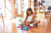 Adorable toddler sitting on the floor. Playing with wooden building blocks at kindergarten