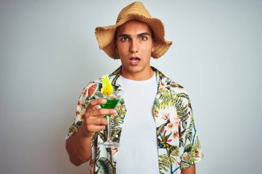 Young handsome man drinking cocktail on holiday over white isolated background scared in shock with a surprise face, afraid and excited with fear expression