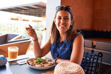 Young beautiful woman sitting at restaurant enjoying summer vacation eating delicious food