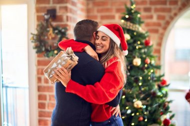 Young beautiful couple smiling happy and confident. Standing holding gift and hugging around christmas tree at home