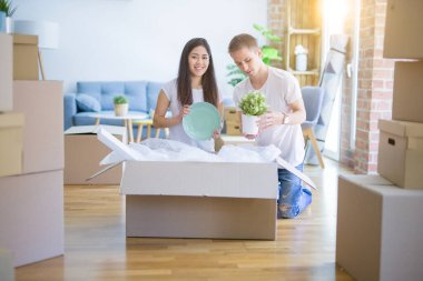 Young beautiful couple at new home around cardboard boxes