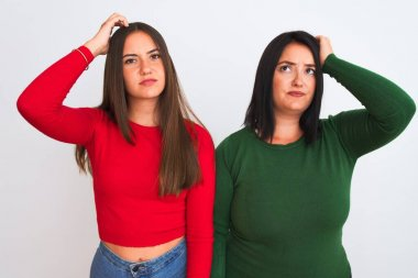 Young beautiful women wearing casual clothes standing over isolated white background confuse and wonder about question. Uncertain with doubt, thinking with hand on head. Pensive concept.