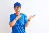 Senior deliverywoman wearing cap and glasses standing over isolated white background amazed and smiling to the camera while presenting with hand and pointing with finger.