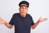 Senior grey-haired man wearing black polo and captain hat over isolated white background clueless and confused expression with arms and hands raised. Doubt concept.