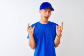 Chinese deliveryman wearing blue t-shirt and cap standing over isolated white background shouting with crazy expression doing rock symbol with hands up. Music star. Heavy concept.