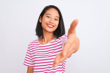Young chinese woman wearing striped t-shirt standing over isolated white background smiling friendly offering handshake as greeting and welcoming. Successful business.