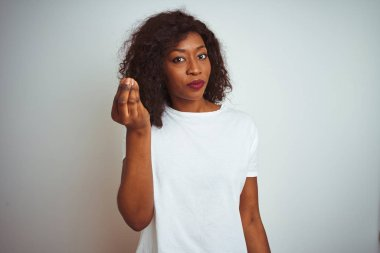 Young african american woman wearing t-shirt standing over isolated white background Doing Italian gesture with hand and fingers confident expression