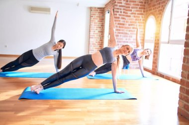 Young beautiful group of sportswomen smiling happy practicing yoga doing side plank pose at gym