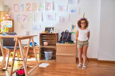 Beautiful toddler wearing glasses and unicorn diadem hanging up draw on the wall at kindergarten