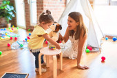 Young beautiful teacher playing with dog doll and toddler holding jar of chocolate balls at kindergarten