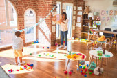 Beautiful teacher and toddler playing basketball using ball and wicker basket around lots of toys at kindergarten