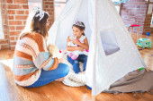 Photo Beautiful teacher and toddler wearing princess crown playing with unicorn doll inside tipi around lots of toys at kindergarten