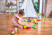 Young beautiful toddler sitting on the floor playing with small cars toys at kindergaten