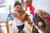 Photo Adorable toddler smiling happy hugging teddy bear around lots of toys at kindergarten
