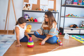 Photo Beautiful teacher and toddler building pyramid using hoops around lots of toys at kindergarten