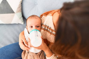 Young beautiful woman and her baby on the sofa at home. Newborn and mother relaxing and resting comfortable drinking milk using feeding bottle