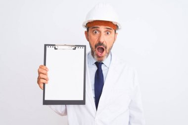 Senior engineer man wearing security helmet holding clipboard over isolated white background scared in shock with a surprise face, afraid and excited with fear expression