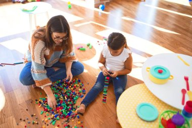 Beautiful teacher and toddler playing with building blocks toy around lots of toys at kindergarten