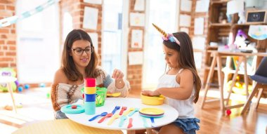Beautiful teacher and toddler smiling happy playing meals using plastic food and cutlery around lots of toys at kindergarten