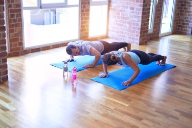 Middle age beautiful sporty couple smiling happy. Practicing yoga doing four-limbed staff pose at gym