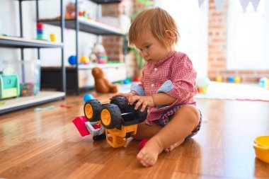 Adorable toddler playing with tractor around lots of toys at kindergarten